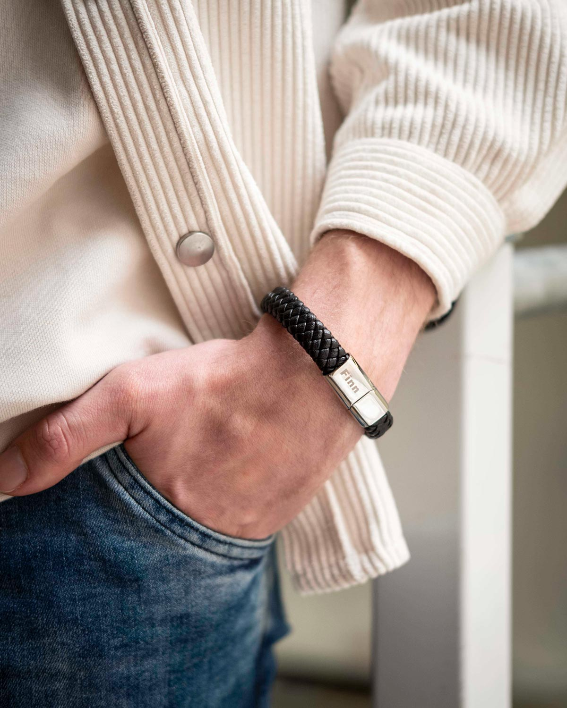 man draagt gevlochten leren armband met gravering