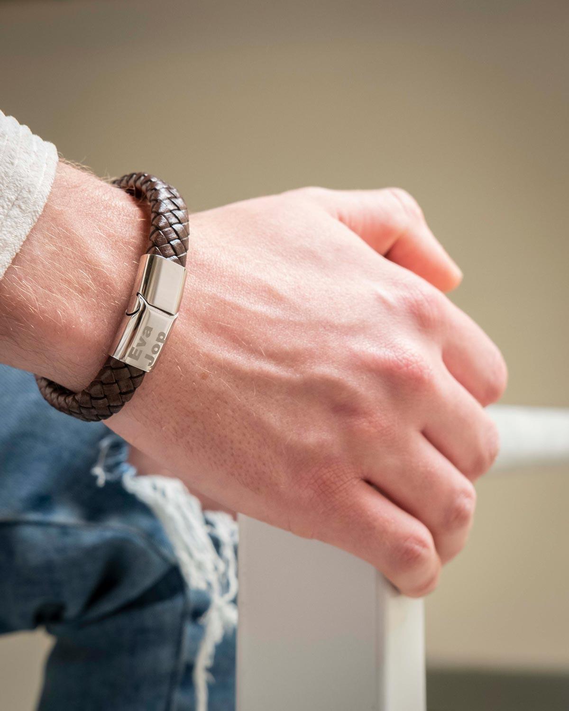 man draagt bruine leren armband met gravering