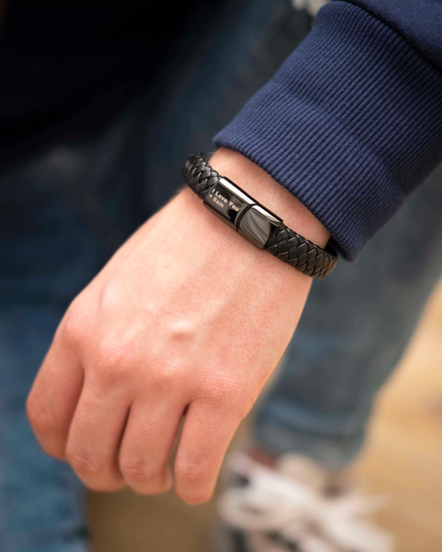 man draagt zwarte leren armband met gravering