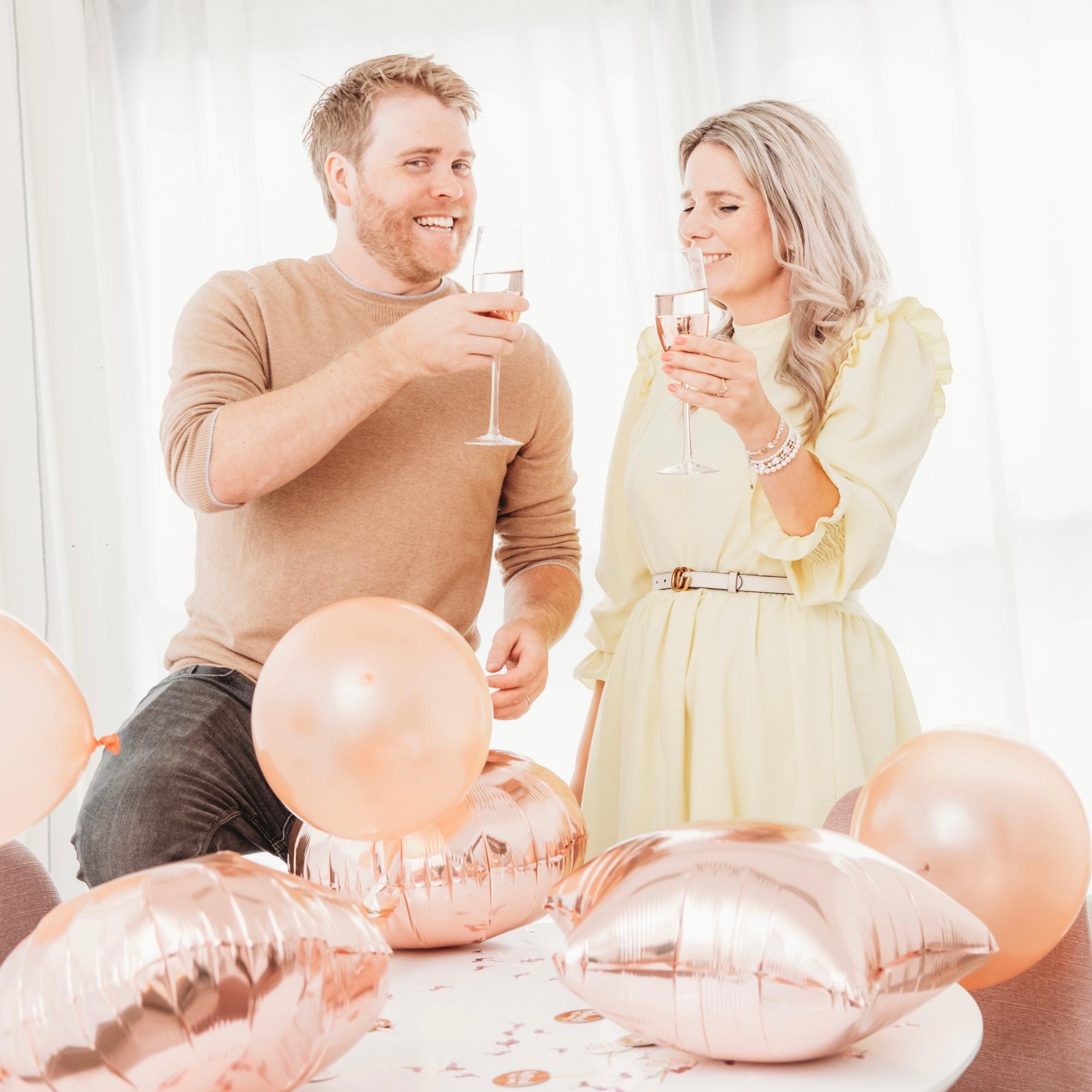 man en vrouw vieren feest met ballonnen en drankje
