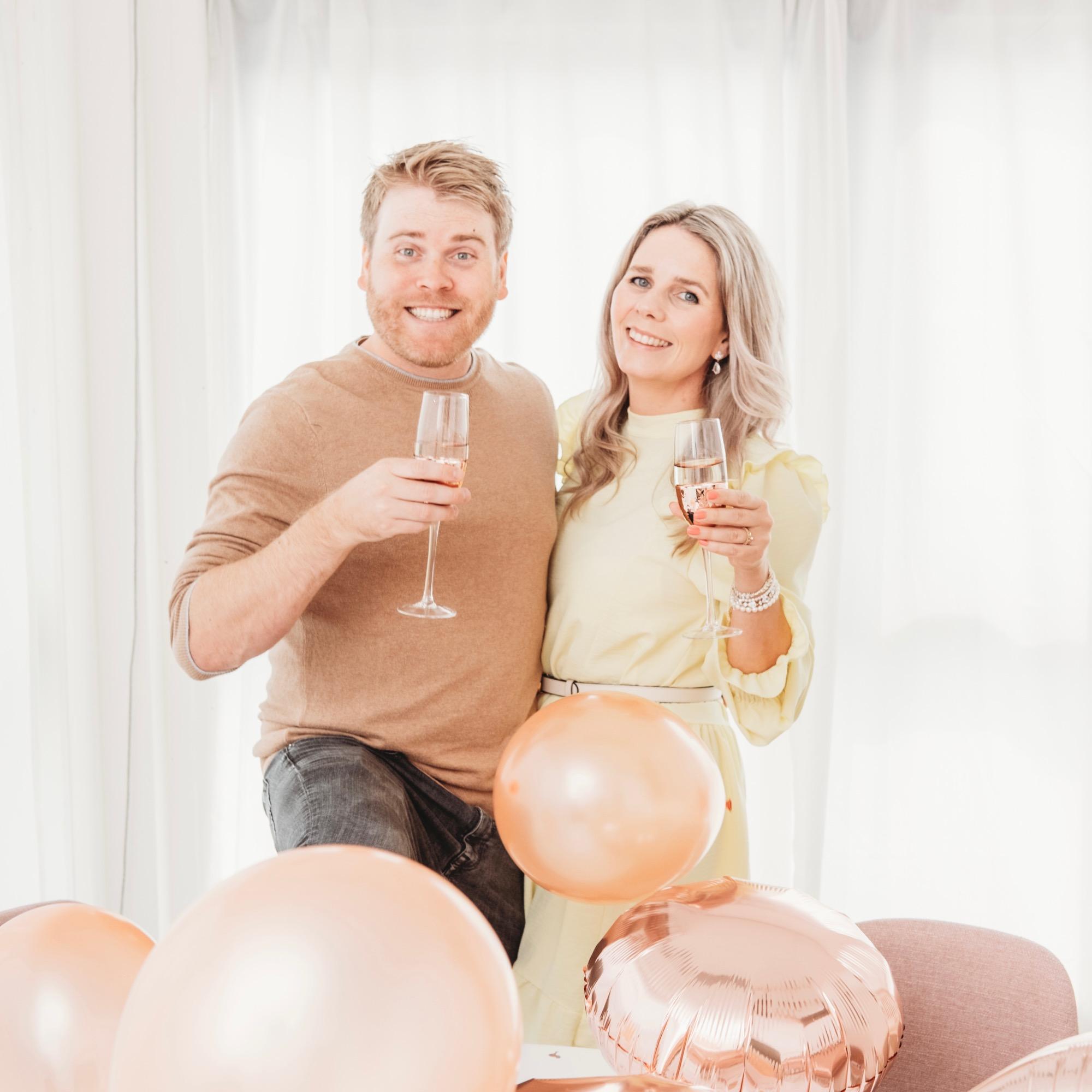 vrolijke man en vrouw met drankje en ballonnen