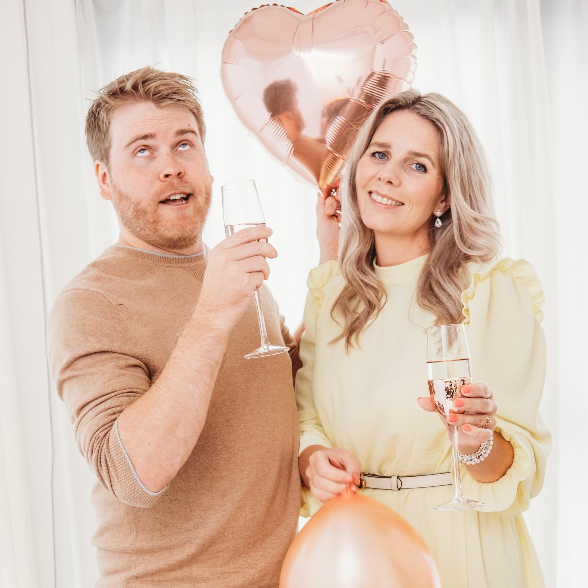 man en vrouw met ballonnen en drankje
