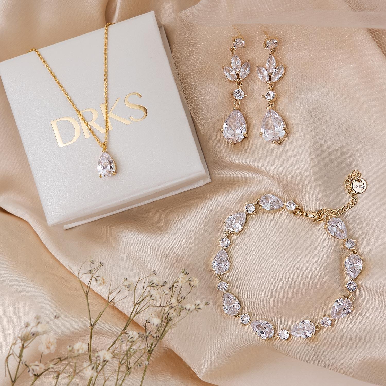 gouden sieraden met steentjes op satijn
