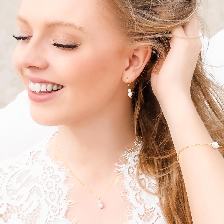 vrouw draagt gouden sieradenset met parels