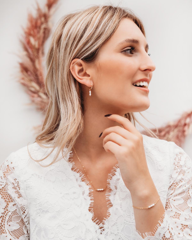vrouw draagt gouden sieraden met pareltjes